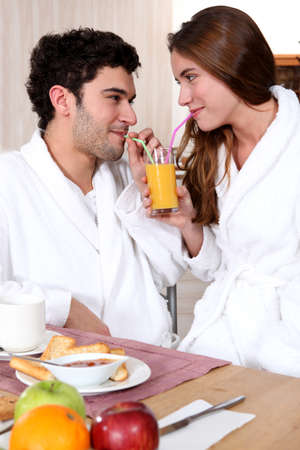 young couple in bathrobe drinking orange juice out of straw photo