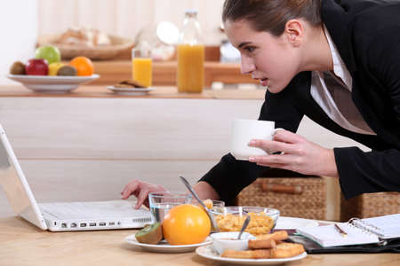 Businesswoman looking at a laptop over breakfast photo