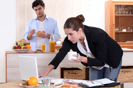 simultaneously: Woman working while eating breakfast Stock Photo
