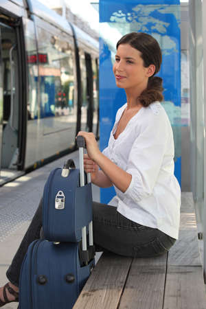 a woman waiting at tram station photo