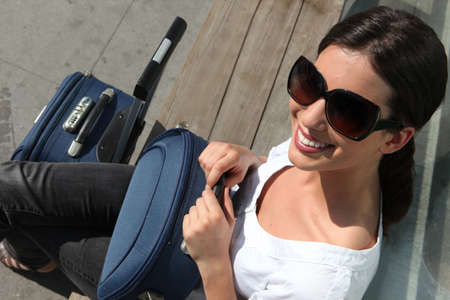 Woman in sunglasses waiting with a suitcase photo