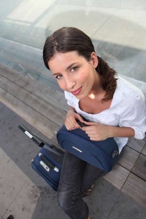 Woman sitting on dock with luggage photo