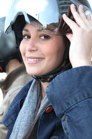 motorcycle helmet: Young woman putting a crash helmet on