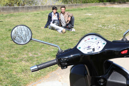 Motorcycle parked on the grass and couple photo