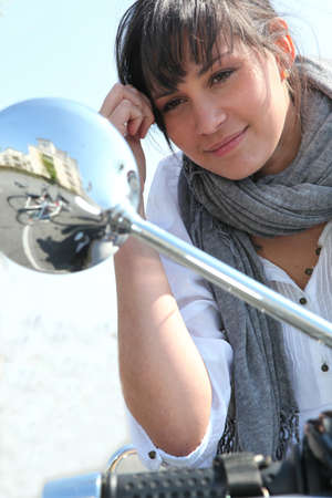 Woman looking into the wing mirror of her moped photo