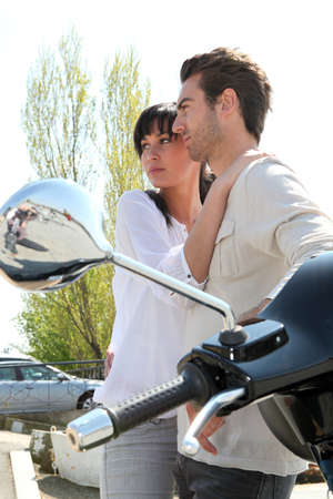 Couple standing next to a parked scooter Stock Photo - 13976995