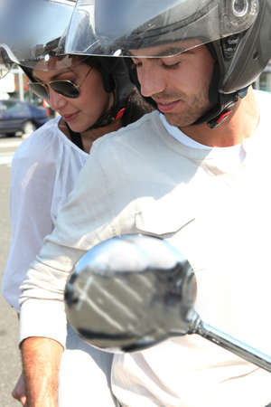 Couple riding a scooter on a sunny day photo