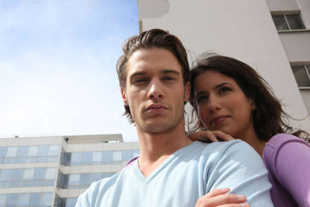 condominium complex: Couple standing in front of a building