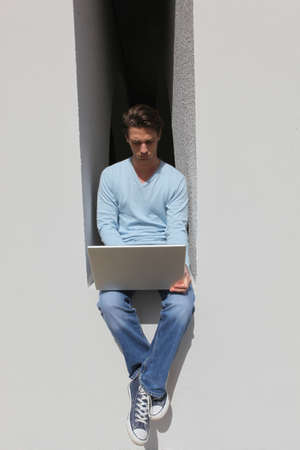 Man sitting on a low wall with laptop photo