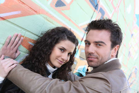 asbo: Attractive couple stood in front of graffiti-ed wall