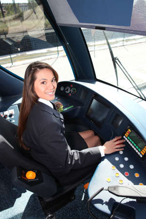 trams: Female tram conductor sat at controls Stock Photo