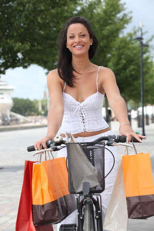 laden: Woman on a pushbike laden down with store bags Stock Photo