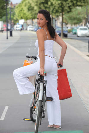 Woman cycling in city with shopping bags photo