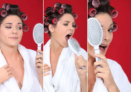 brunette wearing bathrobe with hair curlers holding hairbrush holding  against red background photo