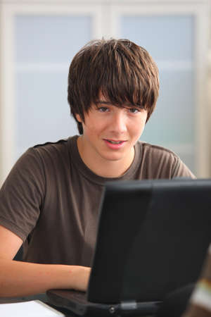 Teenage boy doing his homework on line photo