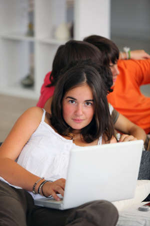 Teenage girl using a laptop at home with friends photo