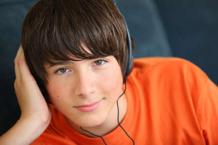 Teenager listening to music on headphones photo