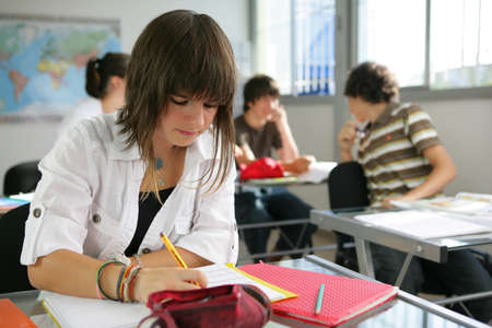 a teenage girl studying in a classroom photo