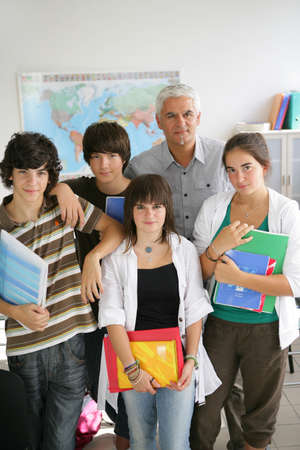 sixteen year old: Teenagers standing with their teacher in a classroom