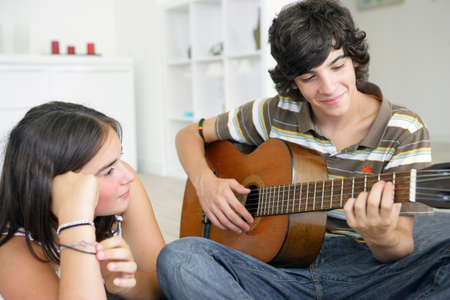 love music: Young teenage couple with a guitar