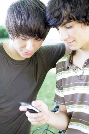 Two male teens reading text message photo