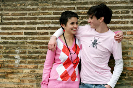 Young couple stood by wall photo