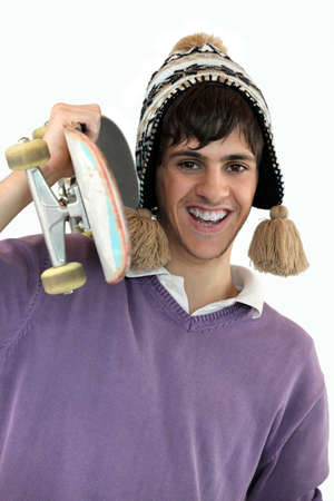 Young man carrying a skateboard photo