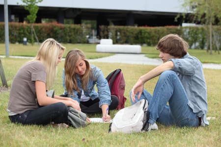 sitting on the ground: Three students studying on the grass