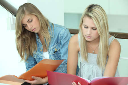 coursework: Two female students with folders Stock Photo