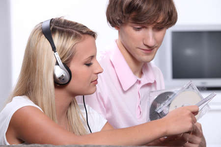 jewel case: Teenage boy and girl sat at home listening to music