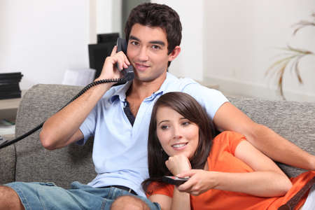 Young couple relaxing on the couch, talking on the telephone and watching television photo