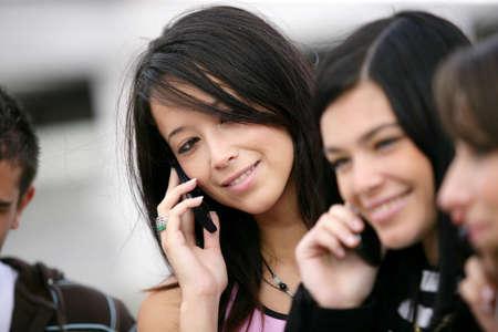 mobiele telefoons: Groep jongeren met behulp van hun mobiele telefoon buitenshuis Stockfoto