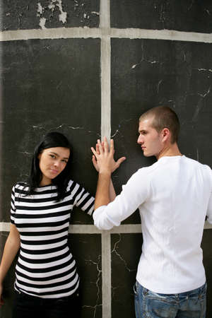 Affectionate couple stood by wall photo