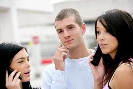 Three teenagers using their mobiles photo