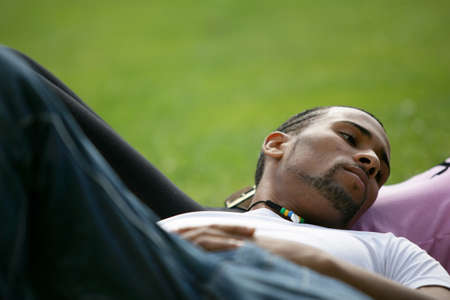calm down: Young man lying in the grass with his girlfriend