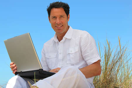 Man smiling on the beach with laptop. photo