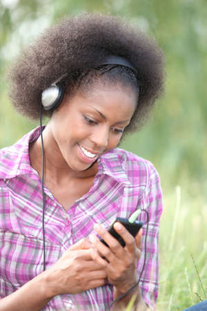Woman listening to music through headphones in field photo
