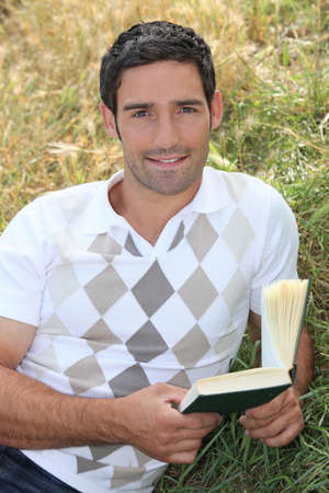 Man laid in field with book in hand photo