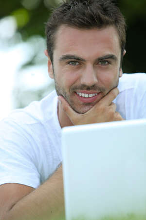 rubbing noses: Man stroking his chin and looking at his laptop