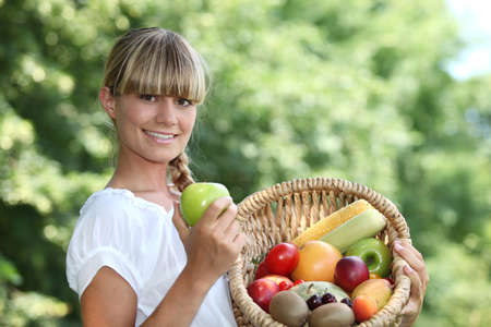Woman holding a basket of fruit photo