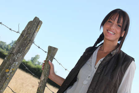 Female farmer stood by barb-wire photo