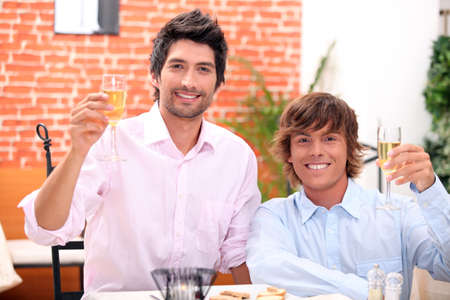 gay couple: homosexual couple celebrating event at restaurant Stock Photo