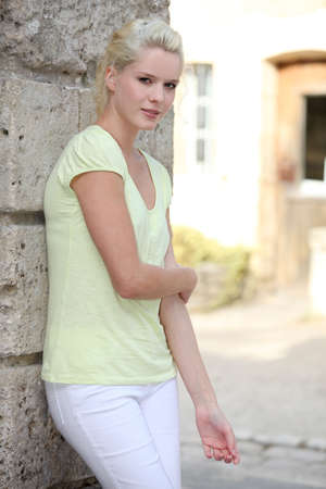 pretty blond womanstanding in front of her house photo