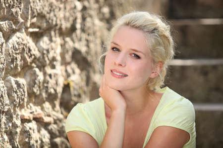 blonde yeux bleus: Blonde femme à côté de mur de pierre Banque d'images