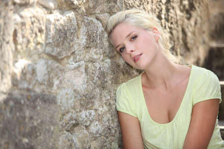 Woman posing against stone wall Stock Photo - 14101247