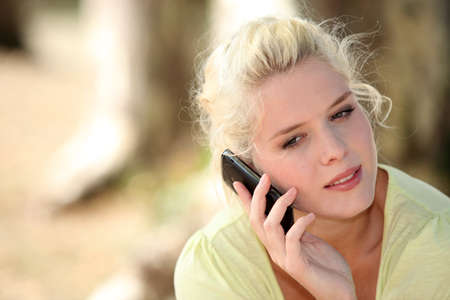 impassive: Neutral woman talking on her mobile phone