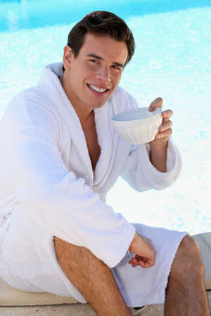 man legs: young guy having coffee at edge of swimming-pool Stock Photo