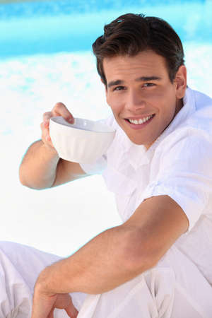 Handsome young man drinking from a china bowl