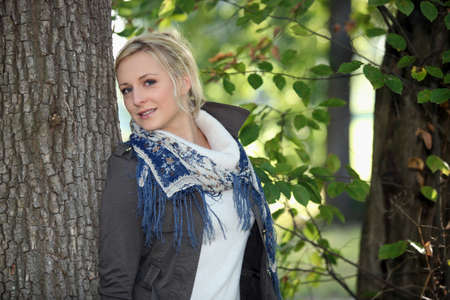 fringes: Woman leaning against tree trunk