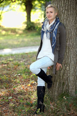 face in tree bark: Woman leaning against tree Stock Photo